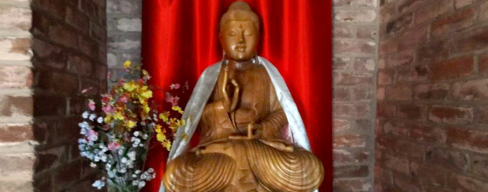 Buddha statue with red curtain and flowers